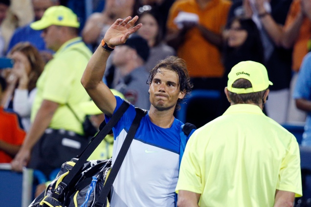 Rafael Nadal, of Spain, waves to the crowd after losing 5-7, 6-4, 7-6 (3) to Feliciano Lopez, of Spain, at the Western & Southern Open tennis tournament, Thursday, Aug. 20, 2015, in Mason, Ohio. (AP Photo/John Minchillo)