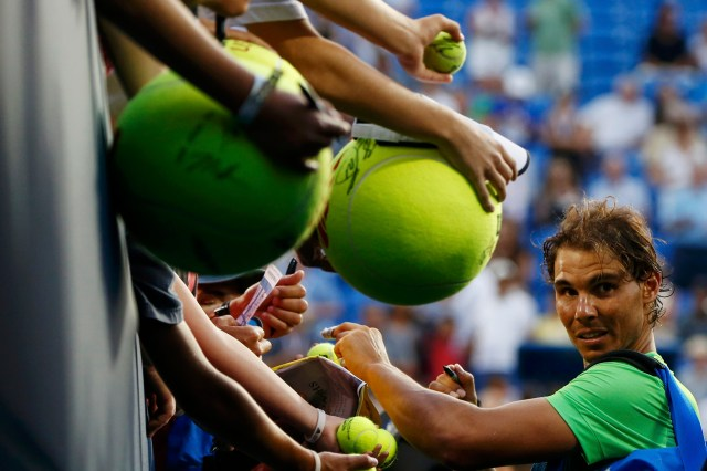 Rafael Nadal of Spain signs autographs for fans following his victory over Diego Schwartzman of Argentina during their second round match at the U.S. Open Championships tennis tournament in New York, September 2, 2015. REUTERS/Shannon Stapleton