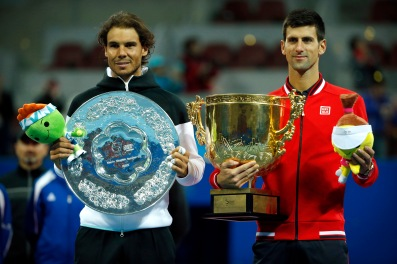 Rafael Nadal of Spain, left, holds the runner's-up trophy and Novak Djokovic of Serbia, right, holds the winner's trophy as they pose for photos after their men's singles final match in the China Open tennis tournament at the National Tennis Stadium in Beijing, Sunday, Oct. 11, 2015. (AP Photo/Mark Schiefelbein)