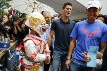 "Tennis players Novak Djokovic of Serbia (C) and Rafael Nadal of Spain (R) walk in a handicraft market before their ""Back To Thailand - Nadal vs Djokovic"" friendly match on Friday, in Bangkok, Thailand, October 1, 2015. REUTERS/Jorge Silva"
