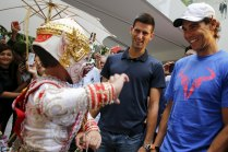 "Tennis players Novak Djokovic of Serbia and Rafael Nadal of Spain (R) look at a Thai folklore dancer as they visit a handicraft market before their ""Back To Thailand - Nadal vs Djokovic"" friendly match on Friday, in Bangkok, Thailand, October 1, 2015. REUTERS/Jorge Silva"
