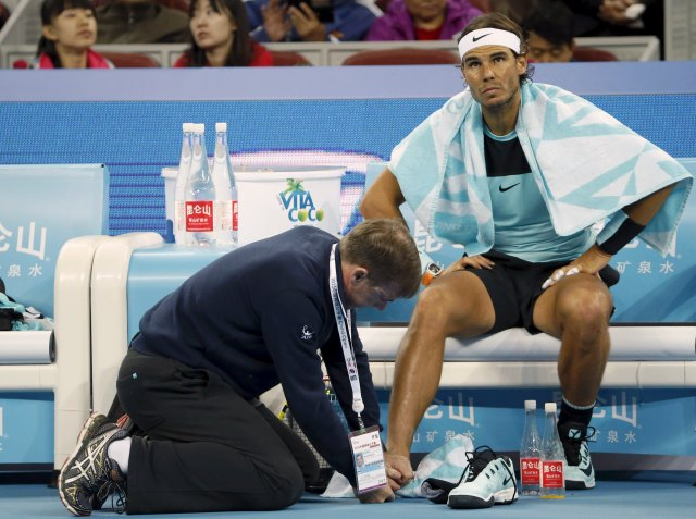Rafa Nadal of Spain receives medical treatment on his foot during the men's singles final match against Novak Djokovic of Serbia at the China Open Tennis Tournament in Beijing, China, October 11, 2015. REUTERS/Kim Kyung-Hoon
