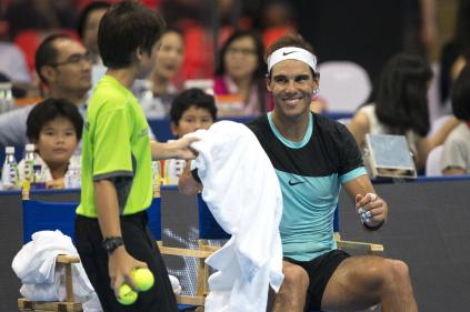 """Rafael Nadal of Spain (R) smiles as he receives a towel from a ball boy during his """"Back To Thailand - Nadal vs Djokovic"""" friendly tennis match in Bangkok, Thailand, October 2, 2015. REUTERS/Athit Perawongmetha"""