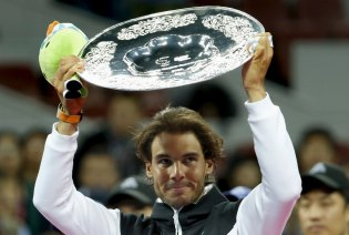 Rafa Nadal of Spain raises his runner-up trophy during the award ceremony after the men's singles final match against Novak Djokovic of Serbia at the China Open Tennis Tournament in Beijing, China, October 11, 2015. World number one Djokovic continued his recent dominance over Nadal when he beat the Spaniard in the final of the China Open to win the tournament for the sixth time on Sunday. REUTERS/Kim Kyung-Hoon