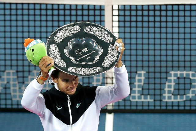 Rafael Nadal of Spain holds up his trophy after his men's singles final match against Novak Djokovic of Serbia in the China Open tennis tournament at the National Tennis Stadium in Beijing, Sunday, Oct. 11, 2015. Djokovic defeated Nadal 6-2, 6-2. (AP Photo/Andy Wong)