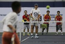 Spain's Rafael Nadal smiles as a Filipino boy returns a shot during a tennis clinic in Makati, south of Manila, Philippines Sunday, Dec. 6, 2015. Nadal is in the country to promote his tennis academy and to compete in the International Premier Tennis League (IPTL). (AP Photo/Aaron Favila)