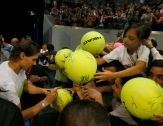 Spain's Rafael Nadal of the Indian Aces autographs large tennis balls of Filipino fans following his win over Canada's Milos Raonic of the Philippine Mavericks in the men's singles match of the 2015 International Premier Tennis League Tuesday, Dec. 8, 2015 at the Mall of Asia Arena at suburban Pasay city south of Manila, Philippines. Nadal won the thrilling shootout 6-5 (7/6). (AP Photo/Bullit Marquez)