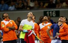 Members of the Indian Aces team, led by Spain's Rafael Nadal, second left, look up to check the score during a break in Nadal's game against the Czech Republic's Tomas Berdych of the UAE Royals in the men's singles of the 2015 International Premier Tennis League Monday, Dec. 7, 2015 at the Mall of Asia Arena in suburban Pasay city, south of Manila, Philippines. Nadal won over Berdych 6-5. (AP Photo/Bullit Marquez)