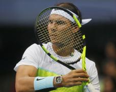 Spain's Rafael Nadal of the Indian Aces is framed by his racket as he returns a shot against Czech Republic's Tomas Berdych of the UAE Royals during the men's singles in the 2015 International Premier Tennis League Monday, Dec. 7, 2015 at the Mall of Asia Arena at suburban Pasay city south of Manila, Philippines. Nadal won over Berdych 6-5. (AP Photo/Bullit Marquez)