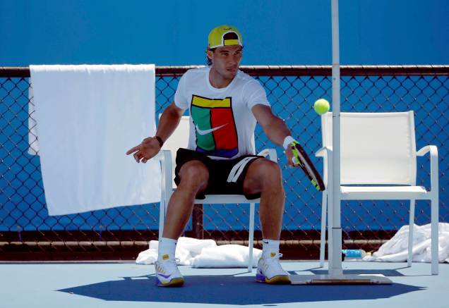 Spain's Rafael Nadal hits a shot as he sits in a chair during a practice session at Melbourne Park, Australia, January 17, 2016. The Australian Open tennis tournament starts January 18. REUTERS/Tyrone Siu