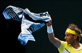 Spain's Rafael Nadal signals a ball boy to bring his other towel during his first round match against Spain's Fernando Verdasco at the Australian Open tennis tournament at Melbourne Park, Australia, January 19, 2016. REUTERS/Thomas Peter