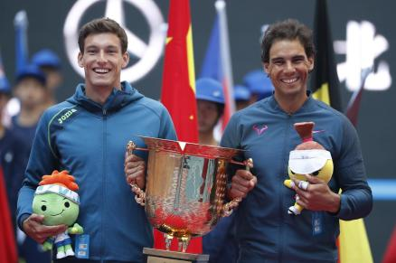 Rafael Nadal, right, and Pablo Carreno Busta of Spain pose with their winning trophy after defeating Jack Sock of the United States and Bernard Tomic of Australia in the men's doubles match at the China Open tennis tournament in Beijing, Sunday, Oct. 9, 2016. (AP Photo/Andy Wong)