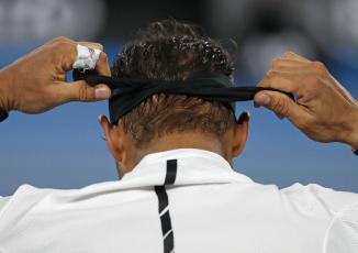Spain's Rafael Nadal ties his headband during a break in his men's singles final against Switzerland's Roger Federer at the Australian Open tennis championships in Melbourne, Australia, Sunday, Jan. 29, 2017. (AP Photo/Dita Alangkara)