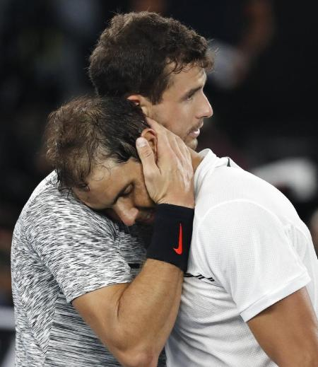 Spain's Rafael Nadal,right, is embraced by Bulgaria's Grigor Dimitrov after winning their semifinal at the Australian Open tennis championships in Melbourne, Australia, Saturday, Jan. 28, 2017. (AP Photo/Kin Cheung)