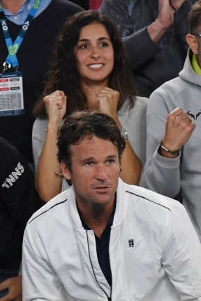 Former Spanish tennis player Carlos Moya (bottom) and Xisca Perello (top), the girlfriend of Spain's Rafael Nadal, cheer as they watch him play against Bulgaria's Grigor Dimitrov during their men's singles semi-final match on day 12 of the Australian Open tennis tournament in Melbourne on January 27, 2017. / AFP / Greg Wood