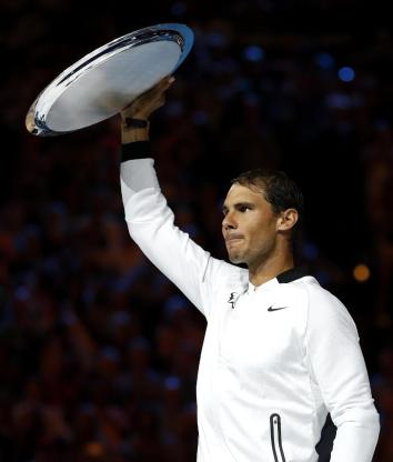 Spain's Rafael Nadal holds up runner-up trophy after losing to Switzerland's Roger Federer in the men's singles final at the Australian Open tennis championships in Melbourne, Australia, Sunday, Jan. 29, 2017. (AP Photo/Dita Alangkara)
