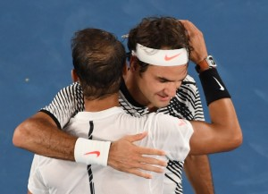 Winner Roger Federer of Switzerland (facing) embraces runner-up Rafael Nadal of Spain following the men's singles final on day 14 of the Australian Open tennis tournament in Melbourne on January 29, 2017. / AFP / SAEED KHAN