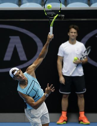 Spain's Rafael Nadal serves as as coach Carlos Moya looks on during a practice session ahead of the Australian Open tennis championships in Melbourne, Australia, Sunday, Jan. 15, 2017. (AP Photo/Aaron Favila)