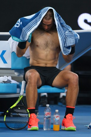 Rafael Nadal of Spain changes his shirt between games in his semifinal match against Grigor Dimitrov of Bulgaria on day 12 of the 2017 Australian Open at Melbourne Park on January 27, 2017 in Melbourne, Australia. (Jan. 26, 2017 - Source: Michael Dodge/Getty Images AsiaPac)