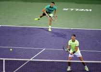INDIAN WELLS, CA - MARCH 10: Bernard Tomic of Australia serves with Rafael Nadal of Spain as they play in the men's doubles against Pablo Carreno Busta of Spain and Joao Sousa of Portugal at Indian Wells Tennis Garden on March 10, 2017 in Indian Wells, California. (Photo by Harry How/Getty Images)