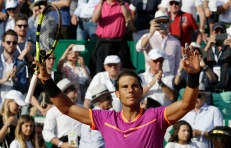 Spain's Rafael Nadal raises his racket after winning his semifinal match against Belgium's David Goffin at the Monte Carlo Tennis Masters tournament in Monaco, Saturday, April, 22, 2017. (AP Photo/Claude Paris)
