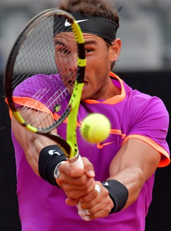 Rafael Nadal of Spain hits a return to Dominic Thiem of Austria during their quarter-final tennis match at the ATP Tennis Open tournament on May 19, 2017 at the Foro Italico in Rome..Austria's Dominic Thiem sent Rafael Nadal crashing out of the Rome Masters with a 6-4, 6-3 quarter-final victory, ending the Spaniard's 17-match winning run. / AFP PHOTO / TIZIANA FABI (May 18, 2017 - Source: AFP)