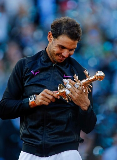 Spanish tennis player Rafael Nadal poses with his trophy as he celebrates his victory over Austrian tennis player Dominic Thiem at the end of their ATP Madrid Open final match in Madrid, on May 14, 2017. .Nadal won 7-6 and 6-4. / AFP PHOTO / OSCAR DEL POZO (May 13, 2017 - Source: AFP)