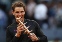 Rafael Nadal of Spain bites the winners trophy after his win over Dominic Thiem of Austria in the final during day nine of the Mutua Madrid Open tennis at La Caja Magica on May 14, 2017 in Madrid, Spain. (May 13, 2017 - Source: Julian Finney/Getty Images Europe)