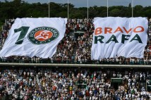People wave a giant flag after Spain's Rafael Nadal won a record 10th French Open title against Stan Wawrinka in their final on June 11 June, 2017 in Paris. / AFP PHOTO / GABRIEL BOUYS (June 10, 2017 - Source: AFP)