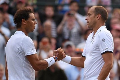 Luxembourg's Gilles Muller (R) shakes hands with Spain's Rafael Nadal after winning their men's singles fourth round match on the seventh day of the 2017 Wimbledon Championships at The All England Lawn Tennis Club in Wimbledon, southwest London, on July 10, 2017..Muller won the match 6-3, 6-4, 3-6, 4-6, 15-13. / AFP PHOTO / Glyn KIRK / RESTRICTED TO EDITORIAL USE (July 9, 2017 - Source: AFP)