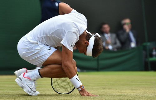Spain's Rafael Nadal looks to his ankle after lunging to play a shot against Luxembourg's Gilles Muller during their men's singles fourth round match on the seventh day of the 2017 Wimbledon Championships at The All England Lawn Tennis Club in Wimbledon, southwest London, on July 10, 2017. / AFP PHOTO / Glyn KIRK / RESTRICTED TO EDITORIAL USE (July 9, 2017 - Source: AFP)