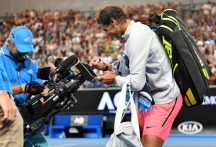 Spain's Rafael Nadal signs an autograph on a cameraman's screen after beating Bosnia's Damir Dzumhur in their men's singles third round match on day five of the Australian Open tennis tournament in Melbourne on January 19, 2018. / AFP PHOTO / SAEED KHAN / -- IMAGE RESTRICTED TO EDITORIAL USE - STRICTLY NO COMMERCIAL USE -- (Photo credit should read SAEED KHAN/AFP/Getty Images)
