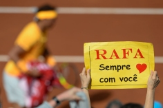 "A supporter holds a placard reading ""With you always Rafa"" in front of Spain's Rafael Nadal during a Barcelona Open ATP tournament tennis match in Barcelona on April 25, 2018. (Photo by Josep LAGO / AFP) (Photo credit should read JOSEP LAGO/AFP/Getty Images)"