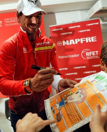 GRAF5253. VALENCIA, 03/04/2018.- El jugador del equipo español de Copa Davis y número uno de la ATP, Rafa Nadal, firma un autógrafo tras un acto promocional organizado por la Diputación de Valencia y Mapfre, en el que participó junto al resto de jugadores del equipo y respondieron a las preguntas formuladas por un grupo de niños. EFE/Manuel Bruque