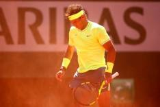 PARIS, FRANCE - JUNE 07: Rafael Nadal of Spain shields himself from the clay kicking up in the wind during his mens singles semi-final match against Roger Federer of Switzerland during Day thirteen of the 2019 French Open at Roland Garros on June 07, 2019 in Paris, France. (Photo by Clive Brunskill/Getty Images)
