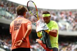 PARIS, FRANCE - JUNE 09: Rafael Nadal of Spain hands his towel to a ball boy during the mens singles final against Dominic Thiem of Austria during Day fifteen of the 2019 French Open at Roland Garros on June 09, 2019 in Paris, France. (Photo by Julian Finney/Getty Images)