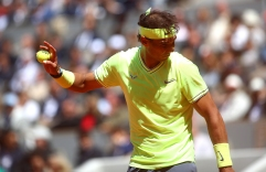 PARIS, FRANCE - JUNE 07: Rafael Nadal of Spain shields himself from the clay kicking up in the wind during his mens singles semi-final match against Roger Federer of Switzerland during Day thirteen of the 2019 French Open at Roland Garros on June 07, 2019 in Paris, France. (Photo by Julian Finney/Getty Images)