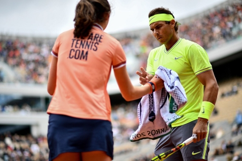 A ballgirl passes a towel to Spain's Rafael Nadal as he plays against Switzerland's Roger Federer during their men's singles semi-final match on day 13 of The Roland Garros 2019 French Open tennis tournament in Paris on June 7, 2019. (Photo by Martin BUREAU / AFP) (Photo credit should read MARTIN BUREAU/AFP/Getty Images)