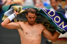 Spain's Rafael Nadal changes his shirt in a break between games against France's Jo-Wilfried Tsonga during their men's singles third round match on the sixth day of the 2019 Wimbledon Championships at The All England Lawn Tennis Club in Wimbledon, southwest London, on July 6, 2019. (Photo by GLYN KIRK / AFP) / RESTRICTED TO EDITORIAL USE (Photo credit should read GLYN KIRK/AFP/Getty Images)