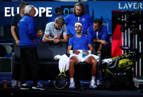 GENEVA, SWITZERLAND - SEPTEMBER 21: Roger Federer of Team Europe and teammates speak to teammate Rafael Nadal as he sits down in his singles match against Milos Raonic of Team World during Day Two of the Laver Cup 2019 at Palexpo on September 21, 2019 in Geneva, Switzerland. The Laver Cup will see six players from the rest of the World competing against their counterparts from Europe. Team World is captained by John McEnroe and Team Europe is captained by Bjorn Borg. The tournament runs from September 20-22. (Photo by Clive Brunskill/Getty Images for Laver Cup)